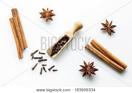 cloves with wooden spoon and cinanmon, star anise and orange slices on white background