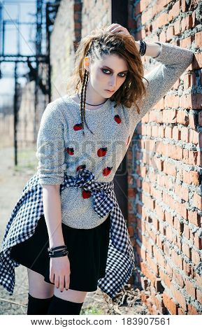 Lovely sad grunge (rock) girl standing near the wall