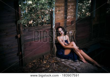 Sad beautiful young woman covered in fabric sits in the old train wagon