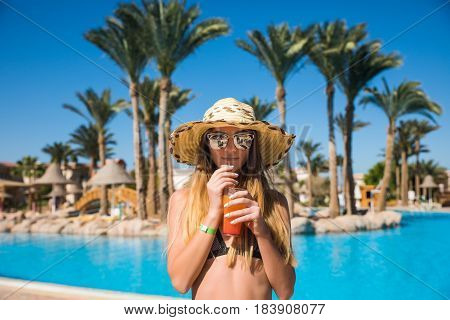 Woman In Bikini And Suglasses With Cocktail Near Nice Blue Pool Background