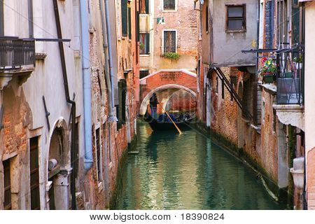 Gondola on small canal among old historic houses in Venice, Italy.