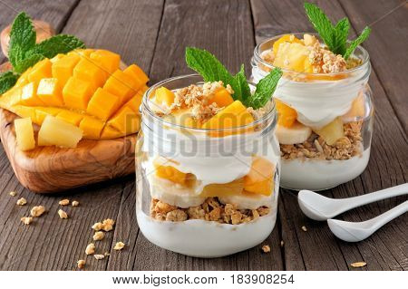 Mango And Pineapple Parfaits In Mason Jars, Scene On A Rustic Wood Background