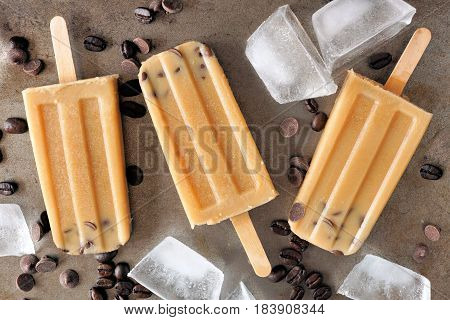 Coffee And Chocolate Popsicles With Ice And Coffee Beans On Dark Metallic Background