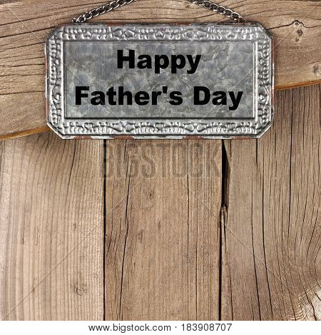 Happy Fathers Day Message On Hanging Metal Sign Against A Rustic Wooden Background