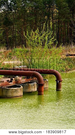 Rusty Metall Pipes Einding In The Water.
