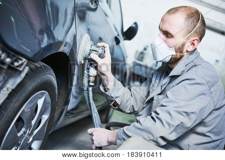 auto repairman grinding automobile car body