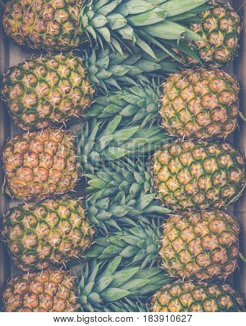 Retro Style Background Texture Of Fresh Pineapples At A Market Stall