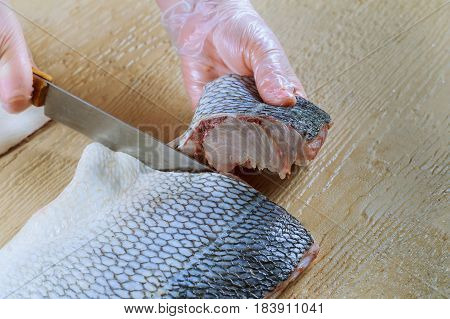 Raw Fish. Cutting Fresh Blyufish Women's Hands.