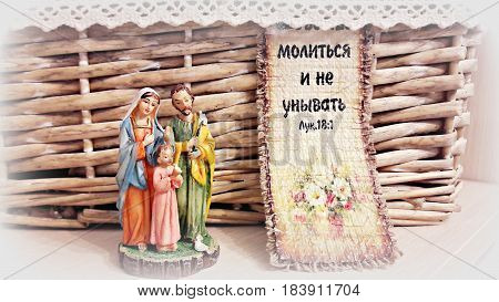 Religious composition: a statuette of Jesus Christ, Mary and Joseph in the background of a wicker basket and text from the Bible
