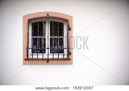 A window with bars on a plain square building.