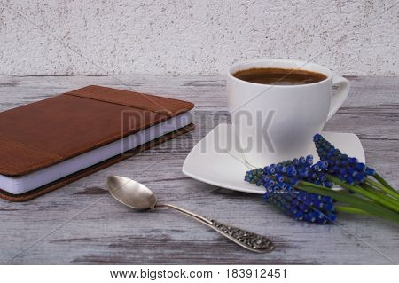 Silver spoon, white cup with coffee, notebook and flowers on a light background.