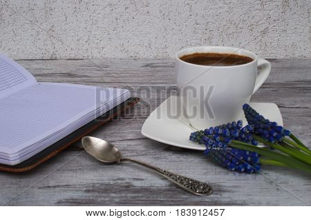 Open notebook, white cup with coffee and flowers on a light background.