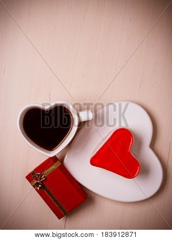 Heart shaped coffee cup jelly cake and red gift box on wooden surface top view copy space for text