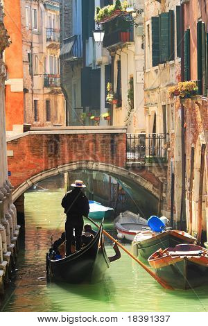 Vertical oriented image of gondola passing on small canal among old historic houses and bridge in Venice, Italy.