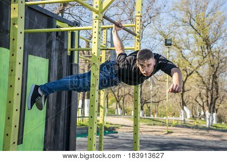 Fit man cross training on monkey bars . Fitness workout on brachiation ladder in an outdoor gym outside. Male athlete hanging on one hand doing back lever one arm