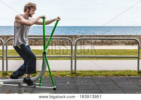 Active man in training suit exercising on elliptical trainer machine at outdoor gym. Sport fitness.