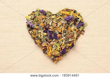 Dried herb leaves heart shaped on burlap surface. Herbaceous dry aromatic plant. Healing herbs herbal medicine concept.