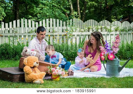 Young couple sitting in the lawn with the children and playing with them in Lviv, Ukraine.