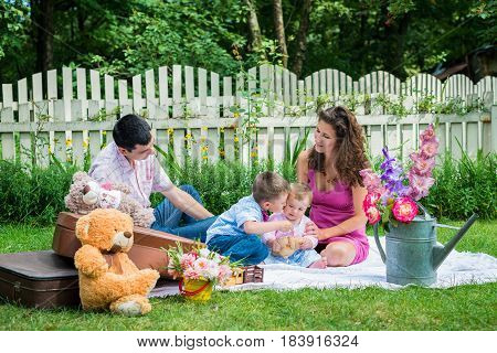 Young couple sitting in the lawn with the children and boy kissing girl in Lviv, Ukraine.