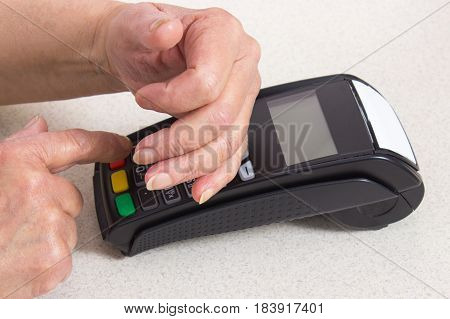 Senior Woman Covering Hands Whilst Entering Personal Identification Number On Payment Terminal