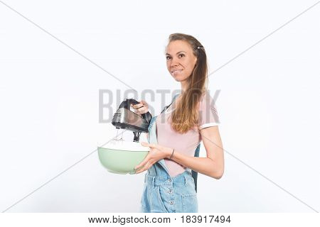 Young attractive smiling woman holding bowl and mixer, cooking in kitchen, making food, daydreaming