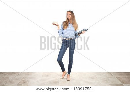 Young working multitasking mother in business clothes, holding booties and documents, making tough choice