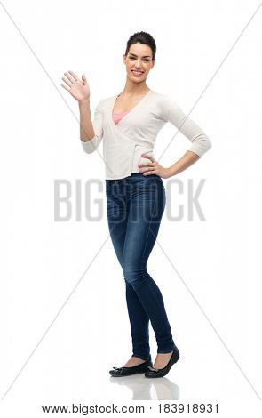 gesture, fashion, portrait and people concept - happy smiling young woman in cardigan and jeans waving hand over white