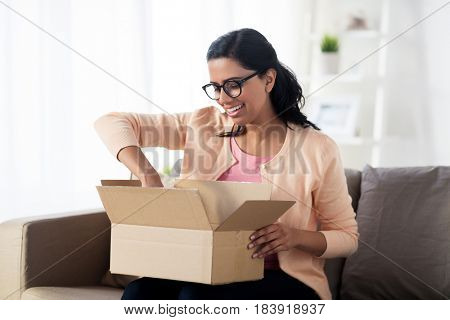 people, delivery, shipping and postal service concept - happy young indian woman holding open cardboard box or parcel at home