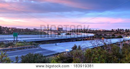 Car headlight trails at sunset traveling across a highway in Newport Beach California