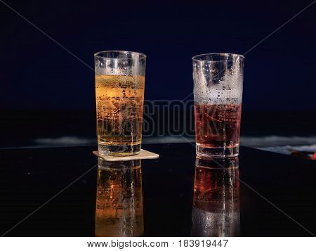 Glass of beer on the table at the beach during night time.