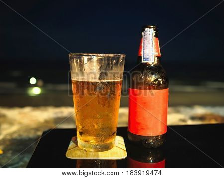 Bottle and glass of beer on the table at the beach during night time.