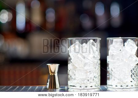 alcohol drinks and luxury concept - two vintage glasses with ice cubes and jigger on bar counter