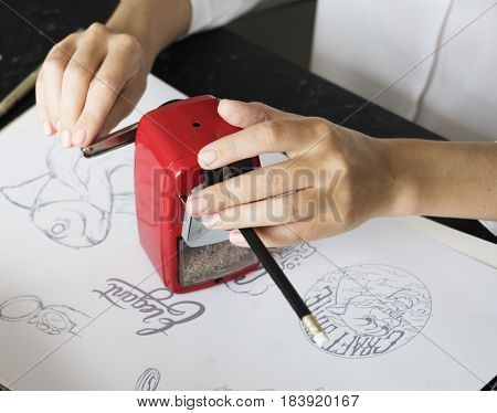 Woman Sharpen Pencil On A Black Table