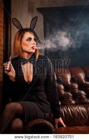 A young attractive girl in a jacket a butterfly tie and bunny ears smokes an electronic cigarette. Femme fatale. Evening makeup smokey eye. She lets out a thick steam from her mouth