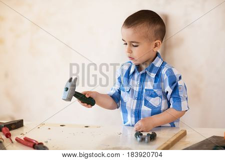 Adorable boy working with wood in workshop close up