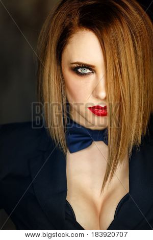 Young attractive girl in a jacket and bow tie looks languidly. Femme fatale. Evening makeup smokey eye. Expressive eyes. Lust