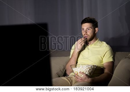 people, mass media, television and entertainment concept - young man watching tv and eating popcorn at night at home