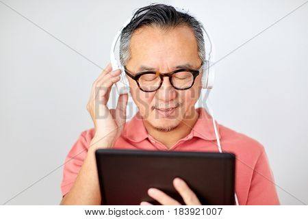 technology, people and lifestyle concept - happy man with tablet pc computer and headphones listening to music