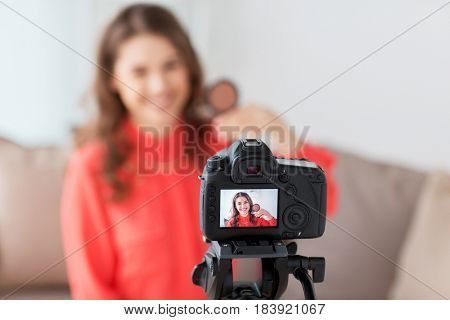 blogging, technology, videoblog, makeup and people concept - happy smiling woman or beauty blogger with bronzer and camera recording tutorial video at home