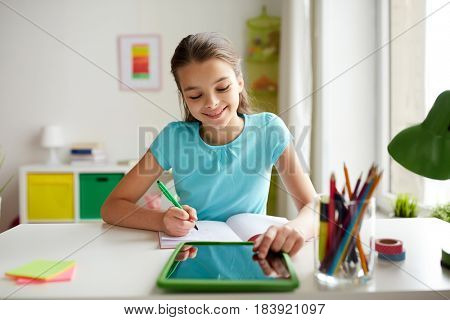 people, children, education and learning concept - happy girl with tablet pc computer writing to notebook at home