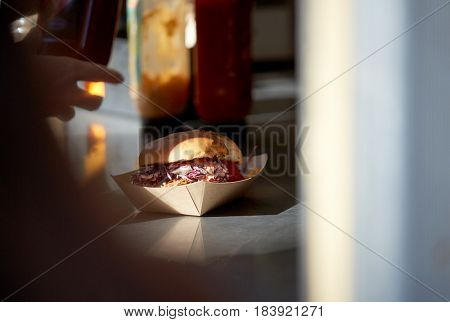 fast food and unhealthy eating concept - hamburger in disposable paper plate on table