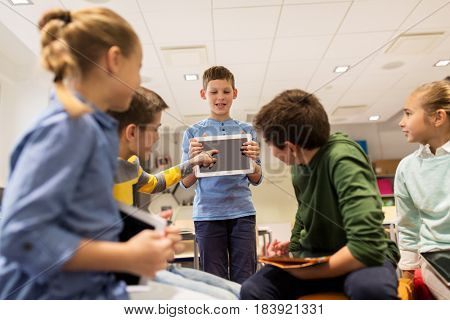 education, learning, technology, children and people concept - happy student boy showing tablet pc computer to group of kids at school