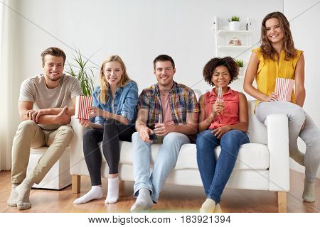 friendship, people and leisure concept - happy friends with popcorn and beer at home