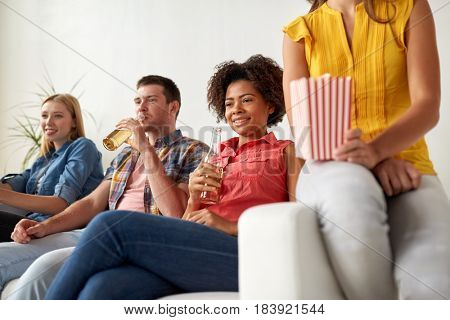 friendship, junk food, people and entertainment concept - happy friends with popcorn and beer watching tv at home