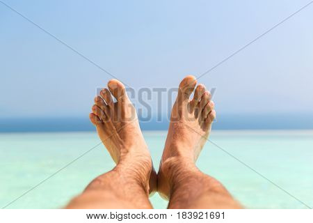 travel, tourism, vacation, people and summer holidays concept - male feet on beach