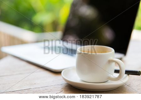 business, drinks and objects concept - close up of coffee cup and laptop on table outdoors