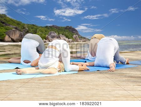 fitness, sport, yoga and healthy lifestyle concept - group of people making ear pressure pose over tropical beach background
