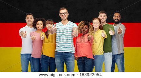 diversity, race, ethnicity, immigration and people concept - international group of happy smiling men and women showing thumbs up over german flag background