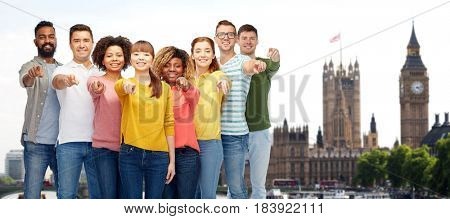 travel, tourism, diversity, and people concept - international group of happy smiling men and women pointing finger on you over london city background