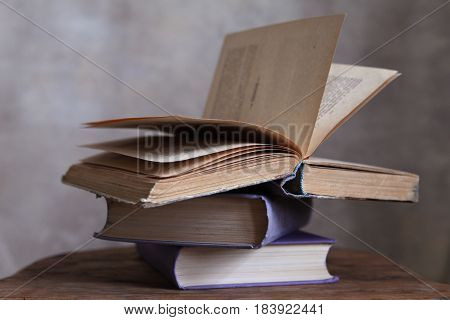Still life with books on the antique table on the gray background in the daylight in close-up